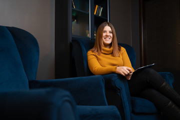 Image of smiling woman psychologist in yellow sweater sitting on blue chair.