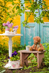 White wooden chair table with a bouquet of lilacs in the spring garden. Recreation area in the shade of trees own garden. Relax in nature. Clean air, peace for creativity and inspiration. fern, apple