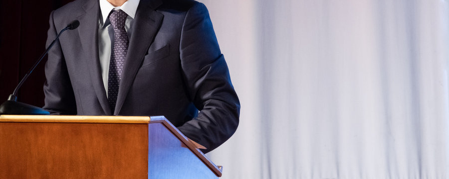 Speech of an abstract man in a suit on stage at the stand for performances. Tribune or cathedra for speaker official, president or professor. Close-up. Copy space.