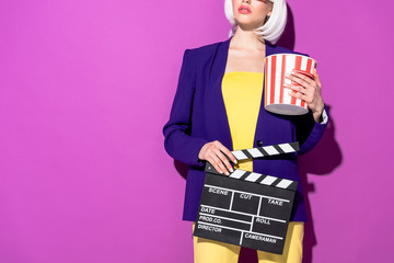 Cropped view of woman in blue jacket holding popcorn and clapperboard on purple background