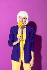 Pensive girl in white wig sniffing flower on purple background