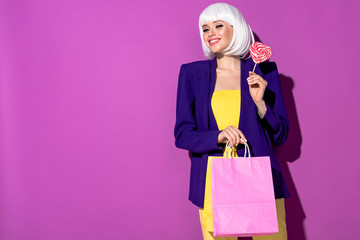 Laughing young woman in white wig holding heart-shaped lollipop and shopping bag on purple background