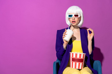 Stylish woman in 3d glasses eating popcorn and drinking soda on purple background
