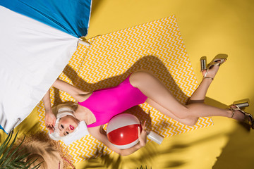 Top view of girl in pink swimsuit and high-heeled shoes lying with ball on yellow towel