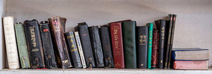 CHIANG MAI, THAILNAD - 24 JANUARY 2019 :  Numerous Holy Bibles sit in a row on wooden shelf. Bookshelf with used prayer books inside..
