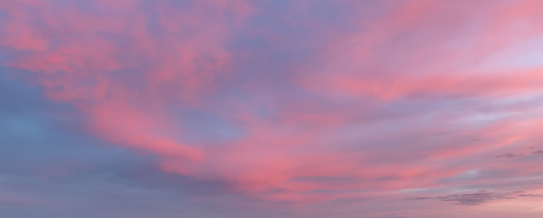 Sunset or sunrise sky clouds, a beautiful pink, purple and blue sky with clouds. Natural cloudscape background. Panoramic view.