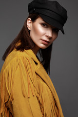 Beautiful girl with a classic make-up and a hairstyle in a fashionable designer jacket and cap, posing in the studio. Beauty face.