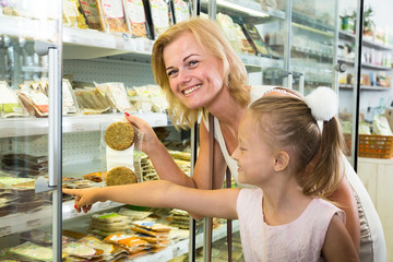 mother with daughter buying chilled foods in supermarket