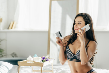 attractive woman holding credit card while talking on smartphone near tray with breakfast