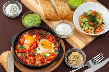 shakshuka in the pan and food on a table