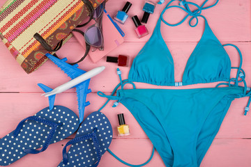 Travel concept - summer women's fashion with blue swimsuit, sunglasses, headphones, flip flops, note pad, little airplane and suitcase