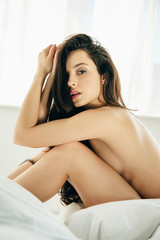 nude brunette young woman sitting on bed and looking at camera