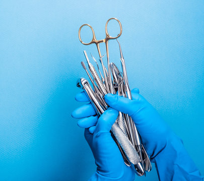 Hand in blue glove holding surgery dental tools on light blue background