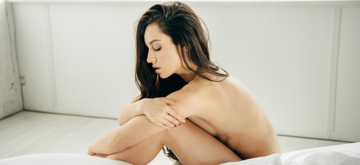 panoramic shot of naked brunette young woman sitting on bed in modern bedroom