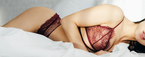 panoramic shot of sexy young woman in red lingerie lying in bedroom