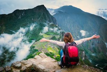 View of girl sitting on the edge of the rock with raised hands and taking pleasure of breathtaking forested mountains landscape of Machupicchu Wall mural