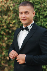 Young groom in suit otside. Handsome man in black suit. Model walking in the park