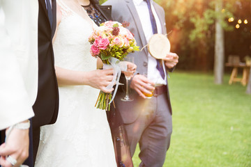 Bride with floral bouquet, and groom in a wedding celebration in a natural outdoor. Empty copy space for Editor's text.