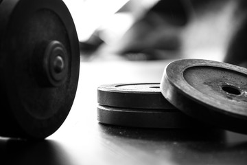 Health gym sport concept. Fitness workout equipment. Dumbbell or barbell on a wooden floor surface. Black and white picture