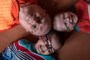 Dad and three brothers in bright colored clothes posing in front of camera with glasses for vision. Children are very similar to each other and happy together. Preschoolers on vacation in their home