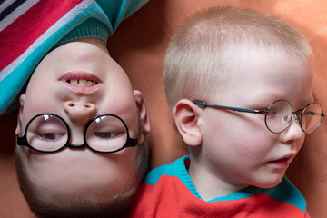 Caucasian blond children in glasses for sight with strong diopters posing in front of camera. Children go to school for visually impaired teens. Teens are friends and happy together
