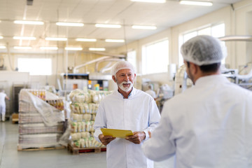 Two employees in sterile uniforms talking about quality of products. Food factory interior. Selective focus on bearded senior worker.