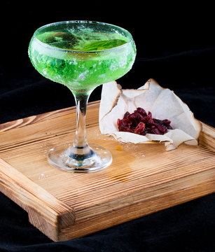 Cocktail Chartreuse on a wooden Board with candied fruit. On dark background