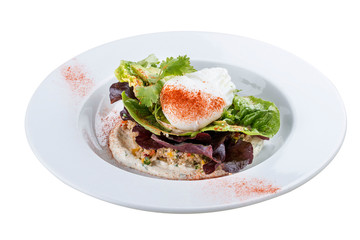 Poached egg with quinoa and salad on a white plate