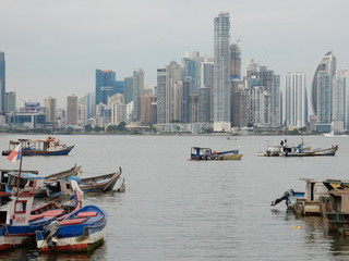 Panama city skyline in a cloudy day with fishing boats moored in the bay, Panama, Central America