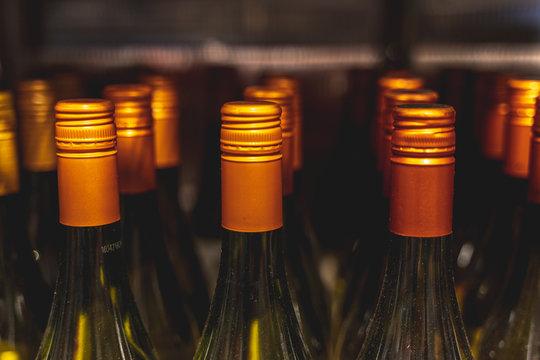 Many wine bottle tops on a store shelf