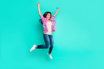 Full length body size photo beautiful funky she her lady hands arms up glad amazed jumping high flight wear casual plaid checkered pink shirt outfit isolated teal bright vivid background