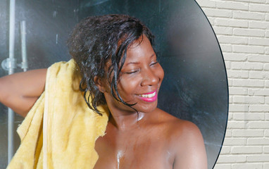 domestic lifestyle mirror reflection portrait of young beautiful black afro American woman wet after having a shower drying hair and body with a towel smiling cheerful