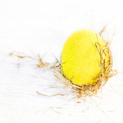 Easter eggs in a wicker nest on white wooden background with  copy space.  Festive decoration. Happy Easter!.