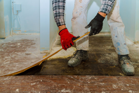Handyman during work of removing oldlaminated parquet flooring