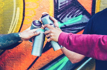 Group of graffiti artists stacking hands while holding spray color can against mural background - Young painter at work - Concept of contemporary art, street art and people youth lifestyle