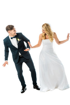 cheerful groom in black elegant suit dancing with happy bride in white wedding dress isolated on white