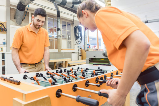 Two carpenters playing table football in work break