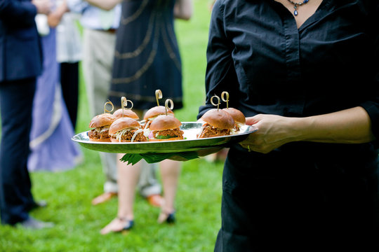 a server holding a tray full of mini pulled pork sandwiches during a catered event