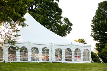 a white wedding tent set up in a lawn surrounded by trees and with the sides down Wall mural