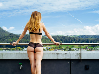 Young woman standing on her balcony in underwear