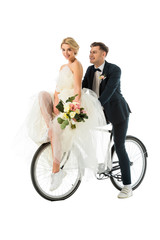 beautiful bride holding wedding bouquet while sitting on bicycle together with groom isolated on white
