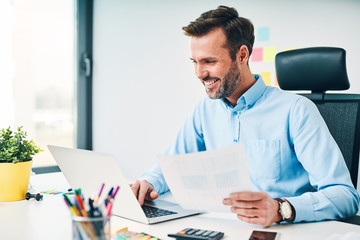 Happy businessman working with financail documents at office