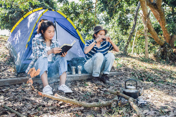 young man and women sitting is reading  book and drinking tea in outside the tent. friendcamping in forest.