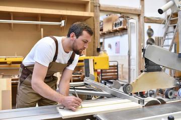 Tischler an einer Säge bei der Arbeit in der Schreinerei // carpenter works in a joinery - workshop for woodworking and sawing