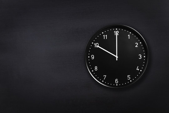 Black wall clock showing ten o'clock on black chalkboard background. Office clock showing 10am or 10pm on black texture