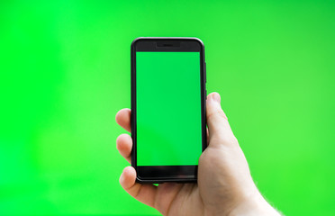 Male hand with Smartphone over green screen. Place for your advertisement.
