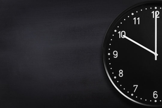 Closeup of black wall clock on black chalkboard texture. Crop image with copyspace