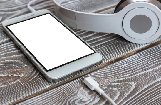 Smartphone, headphones, charger on wooden background. technology, Internet, listening to music.