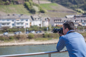 Man photographing castles on Rhine River