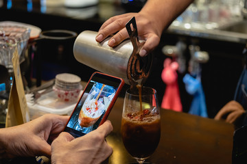 Man taking a photo of barista pour red ruby shake coffee with smartphone